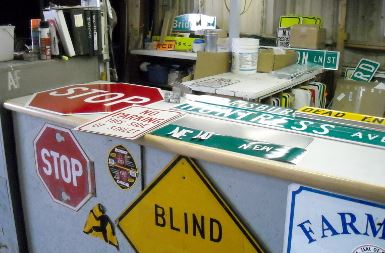 Street signs all over the desk at the sign shop
